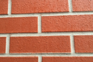 Shown is a paint-like product applied fewer than two years before the photo was taken. The color is single-toned, and the coating has blisters in it. The mortar also has a paint-like product applied. These products are not approved masonry stains.